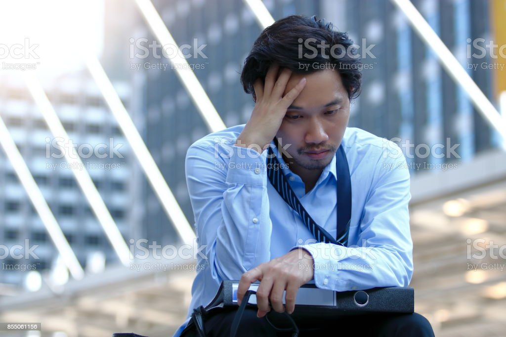 Frustrated stressed young Asian business man touching head and feeling tired or sad his job stock photo