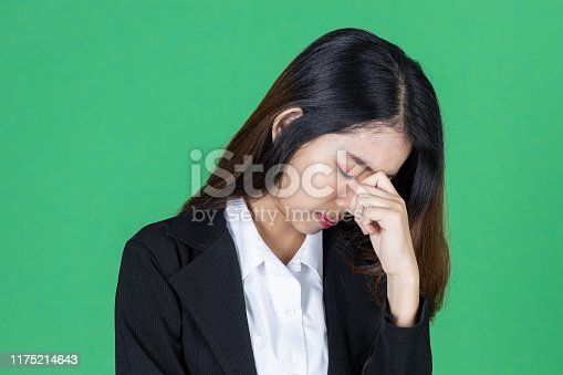 491747470 istock photo Frustrated stressed young Asian business woman with hands on face in depression on green isolated background. 1175214643