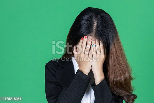491747470 istock photo Frustrated stressed young Asian business woman with hands on face in depression on green isolated background. 1175218031