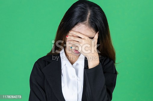 491747470 istock photo Frustrated stressed young Asian business woman with hands on face in depression on green isolated background. 1178264273