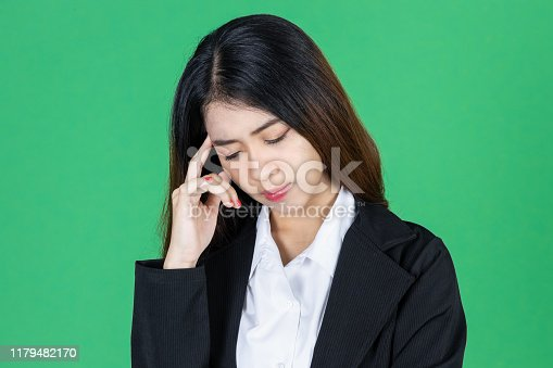 491747470 istock photo Frustrated stressed young Asian business woman with hands on face in depression on green isolated background. 1179482170