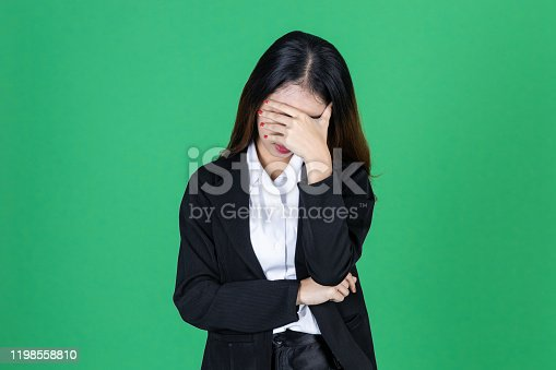 491747470 istock photo Frustrated stressed young Asian business woman with hands on face in depression on green isolated background. 1198558810