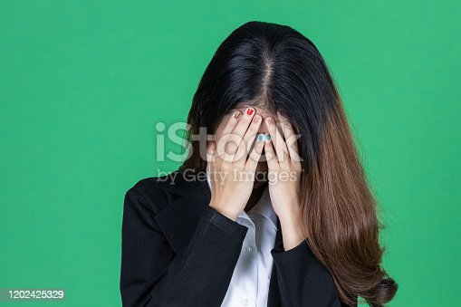 491747470 istock photo Frustrated stressed young Asian business woman with hands on face in depression on green isolated background. 1202425329