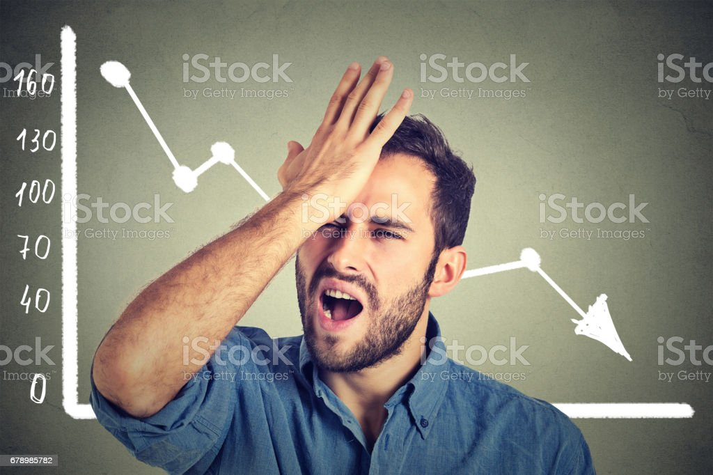 frustrated stressed young man desperate with financial market chart graphic going down on grey office wall background stock photo
