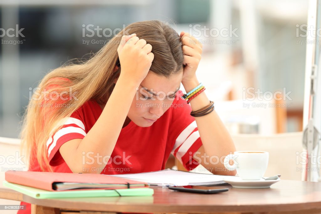 Frustrated student trying to understand notes in a bar stock photo