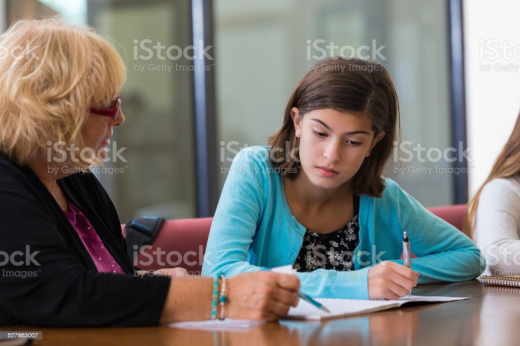 Frustrated student working with tutor on math assignment after school stock photo