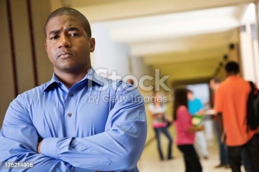 istock Frustrated teacher outside classroom in high school hallway 175214915