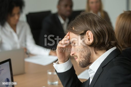 istock Frustrated tired businessman having strong headache at diverse team meeting 958531388