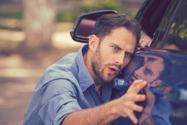 frustrated upset young man looking at scratches and dents on his car outdoors - imperfection stock photos and pictures