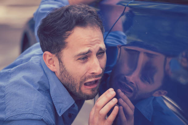 frustrated upset young man looking at scratches and dents on his car outdoors - auto body repair stock photos and pictures