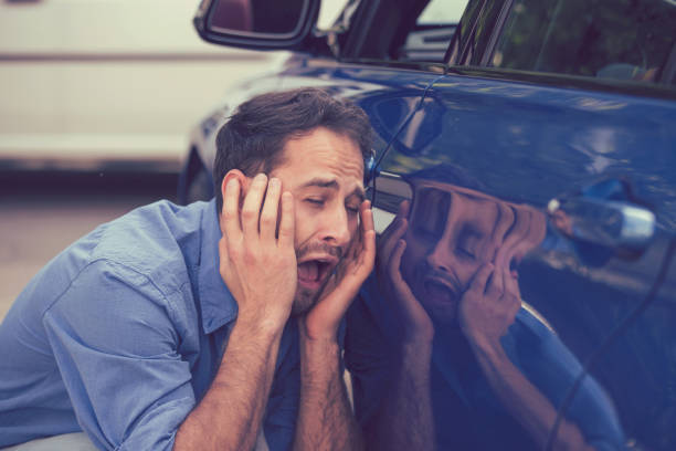 Frustrated upset young man looking at scratches and dents on his car outdoors Upset driver after car accident car crash on parking stock pictures, royalty-free photos & images