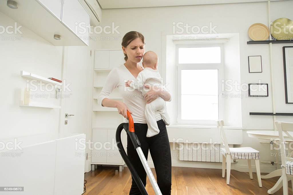 Frustrated woman cleaning the carpet holding a newborn stock photo