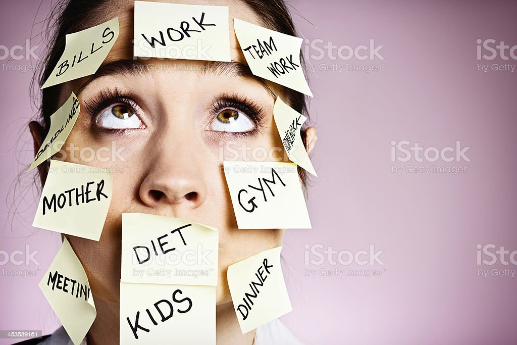 Frustrated woman covered in stiocky reminders rolls her eyes stock photo