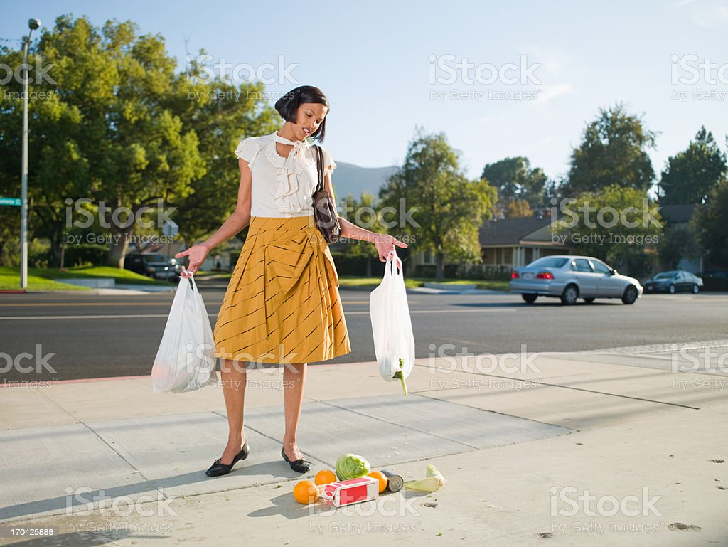 Frustrated woman dropping groceries on sidewalk stock photo