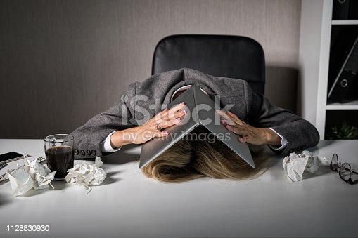 istock Frustrated woman hiding under laptop in office 1128830930