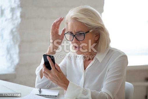 istock Frustrated woman hold cellphone having device troubles 1174413998