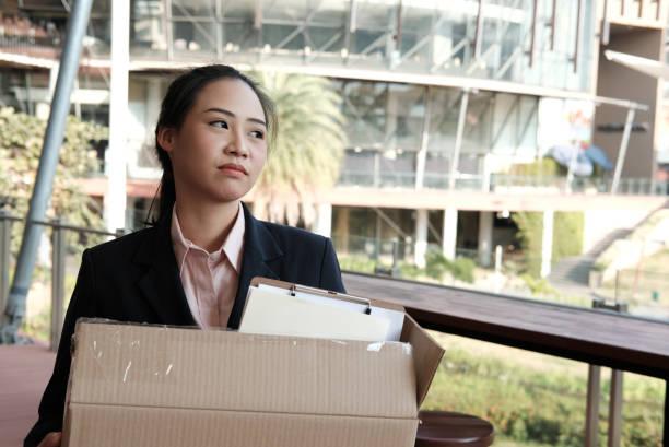 frustrierte Frau mit Karton mit persönlichen Gegenständen nach gefeuert & Entlassung durch den Arbeitgeber. Rücktritt-Konzept – Foto