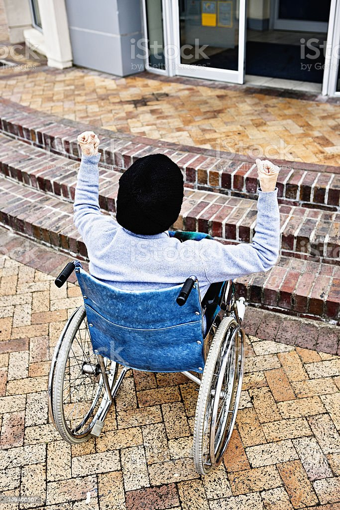 Frustrated woman in wheelchair shakes fists at steps barring her royalty-free stock photo