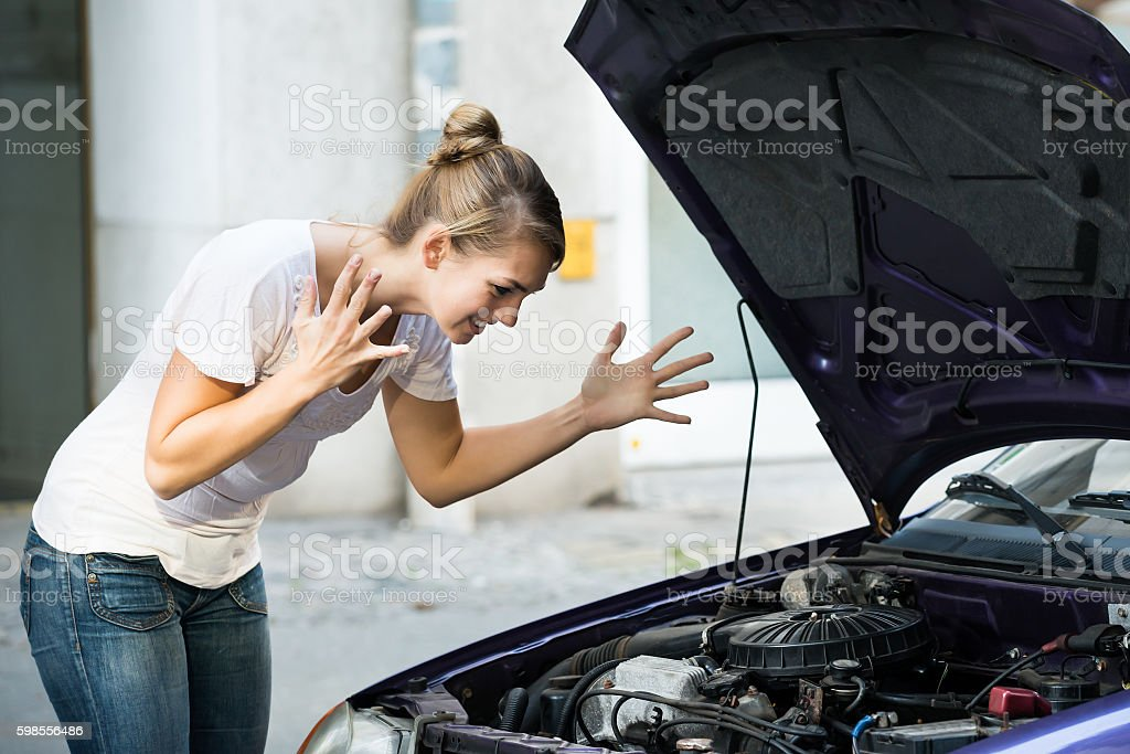 Frustrated Woman Looking At Broken Down Car Engine stock photo