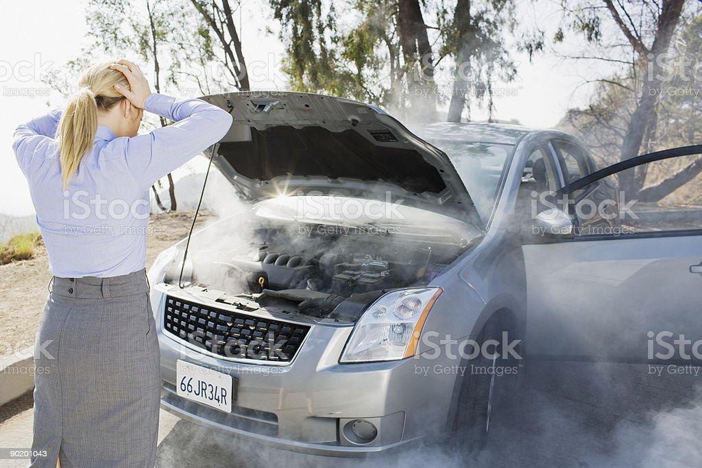 Frustrated woman looking at smoking car engine royalty-free stock photo