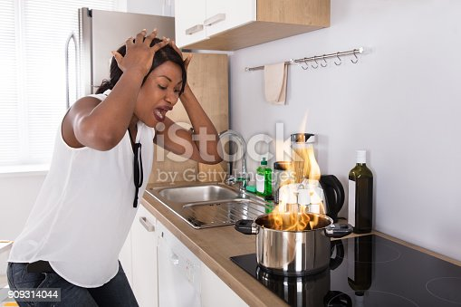 istock Frustrated Woman Looking At Utensil On Fire 909314044