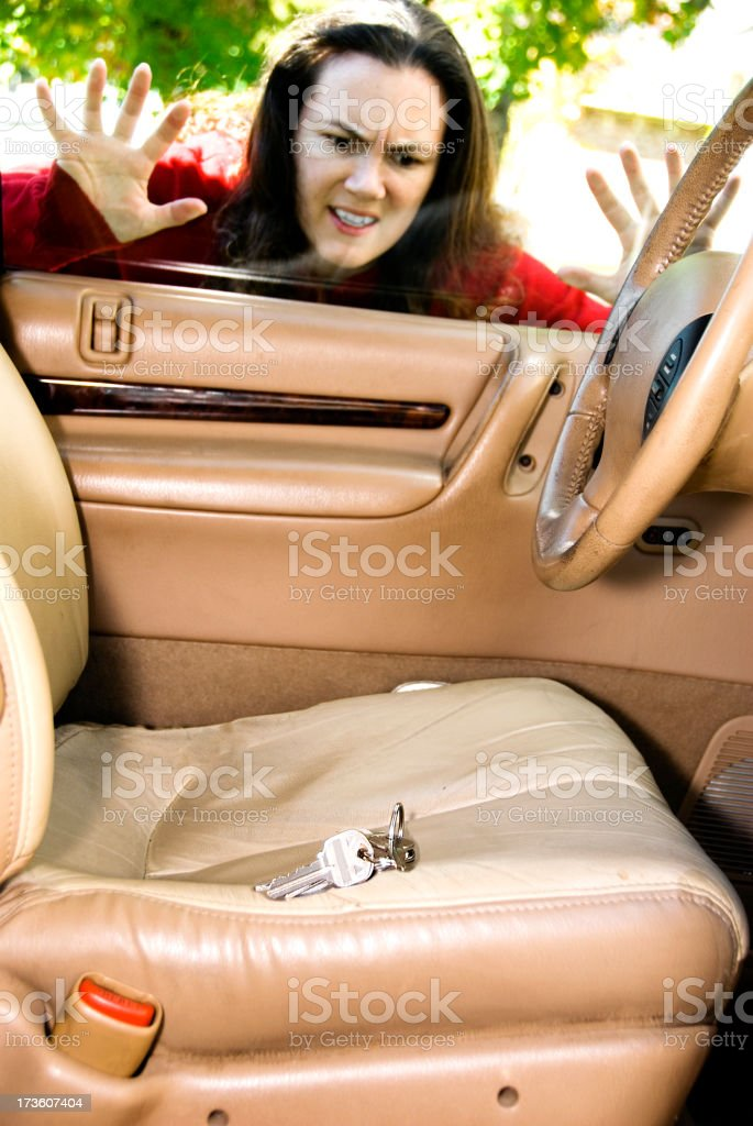 Frustrated woman looking inside locked car with keys on seat stock photo