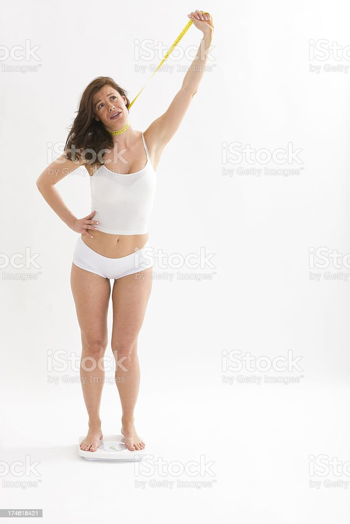 Frustrated woman on scales royalty-free stock photo