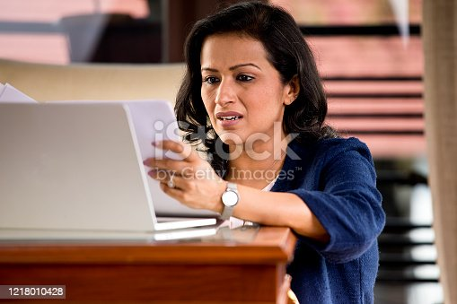 187928332 istock photo Frustrated woman reading document at home office 1218010428