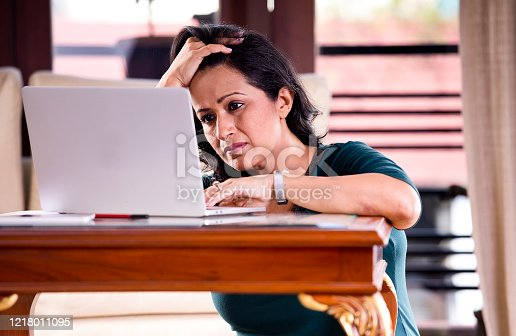 187928332 istock photo Frustrated woman reading document at home office 1218011095