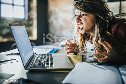 Angry freelance worker feeling displeased after reading an e-mail on a computer.