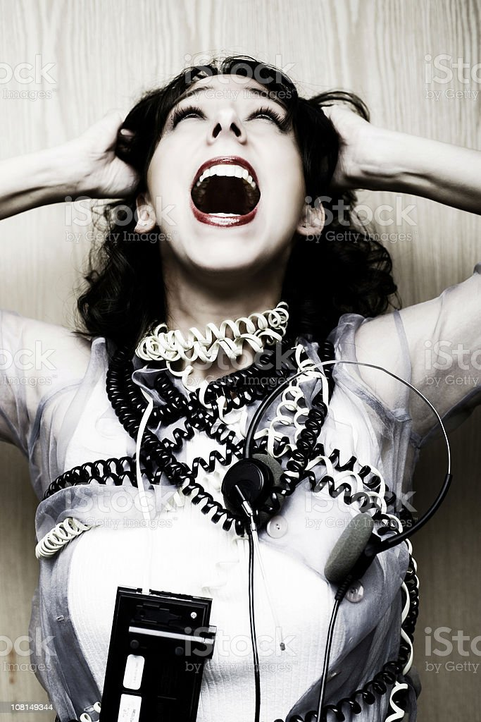Frustrated Woman Screaming and Tied Up in Telephone Cords stock photo