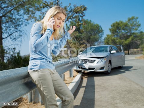 istock Frustrated woman using cell phone next to car wrecked on guardrail 90201035