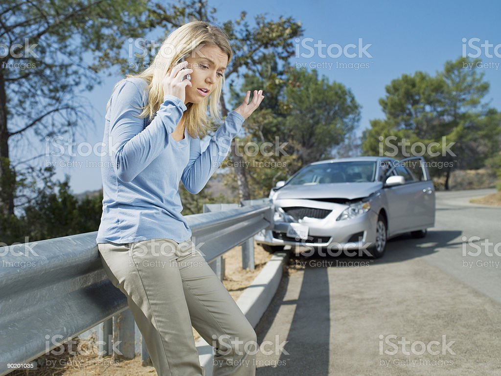 Frustrated woman using cell phone next to car wrecked on guardrail stock photo