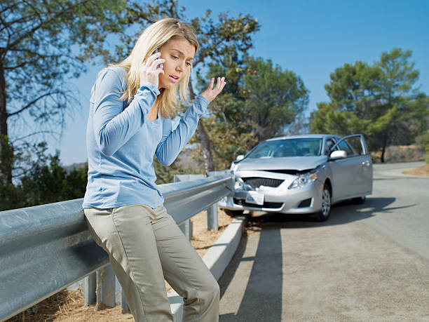 frustrated woman using cell phone next to car wrecked on guardrail - car accident stock photos and pictures