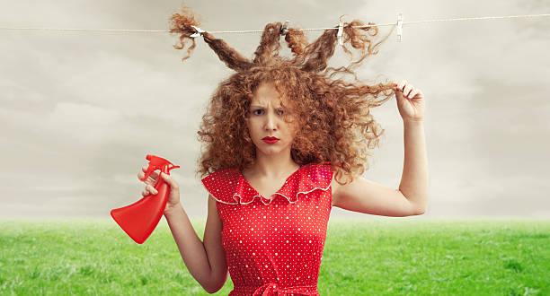 frustrated woman with her hair tied to clothesline and messy - kabarık saç stok fotoğraflar ve resimler
