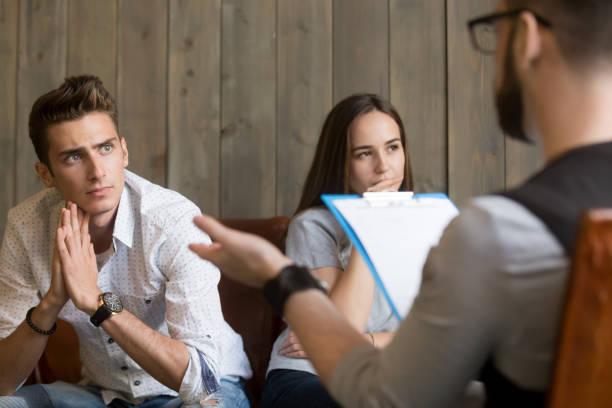 Hombre joven preocupado frustrado escuchando psicólogo, concepto de Consejería de pareja - foto de stock