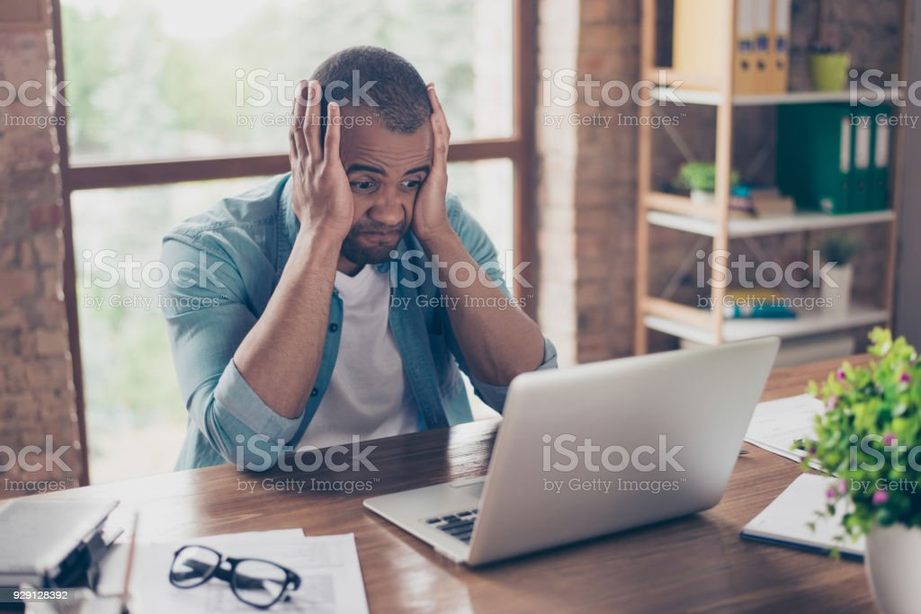 Frustrated young african entrepreneur with sad grimace in front of his laptop in office, noticed a big mistake he did, holding his face with arms palms, wearing jeans casual smart stock photo