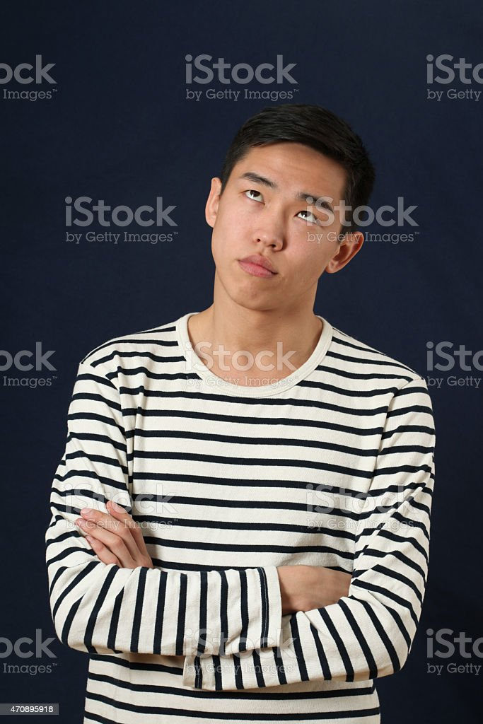 Frustrated young Asian man with crossed hands rolling eyes up stock photo