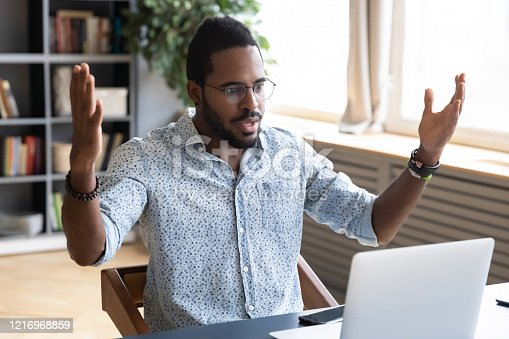857213750 istock photo Frustrated young biracial man feeling shocked about online news. 1216968859