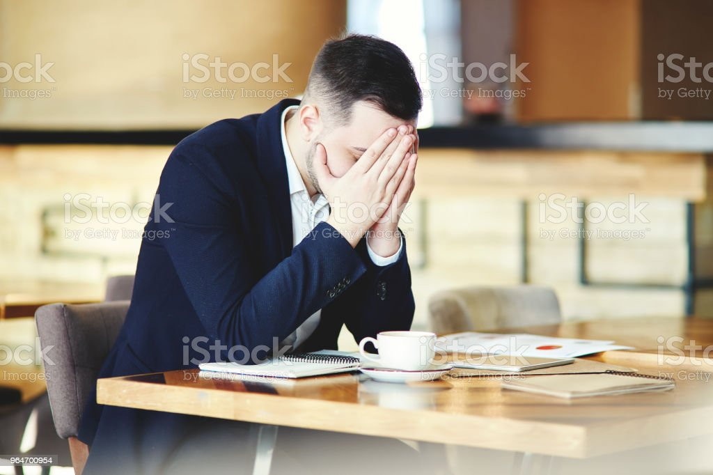 Frustrated young businessman in suit sitting at table in cafe with his hands over face, feeling stressed and exhausted royalty-free stock photo
