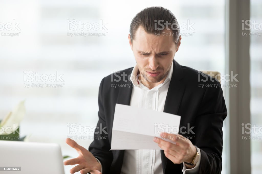 Frustrated young businessman looking at confusing letter in office. stock photo