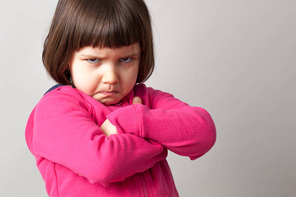 frustrated young child sulking with crossed arms and dirty look unhappy boyish 4-year old girl expressing disagreement with body language anger stock pictures, royalty-free photos & images