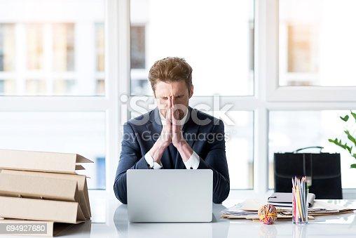 932342408istockphoto Frustrated young employee is working wearily 694927680