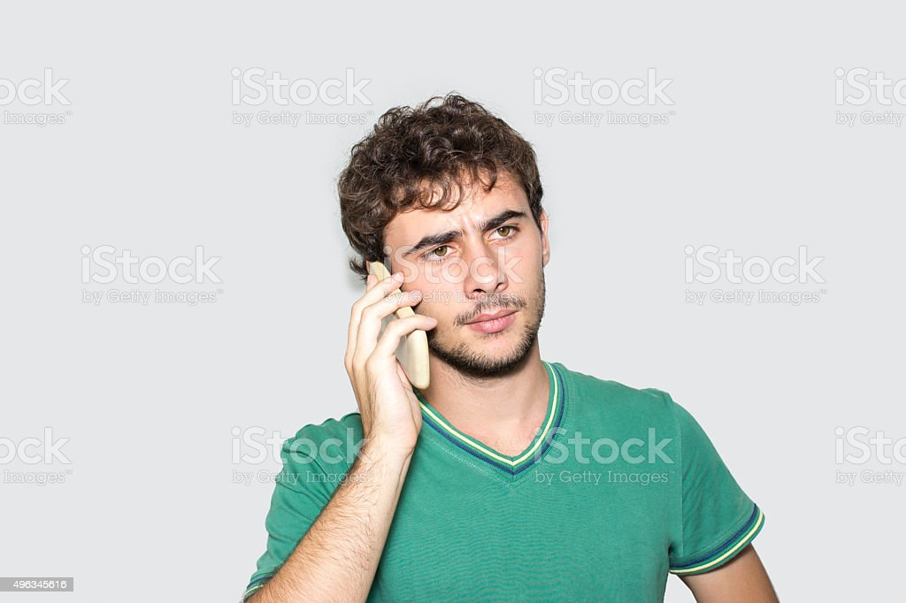 Frustrato Giovane Uomo Parla Al Telefono Su Sfondo Grigio