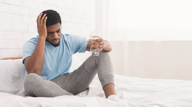 Frustrated young man touching his head and keeping eyes closed Feeling unwell, hangover. Frustrated young african-american man touching his head, holding glass of water in bed, copy space aftereffect stock pictures, royalty-free photos & images