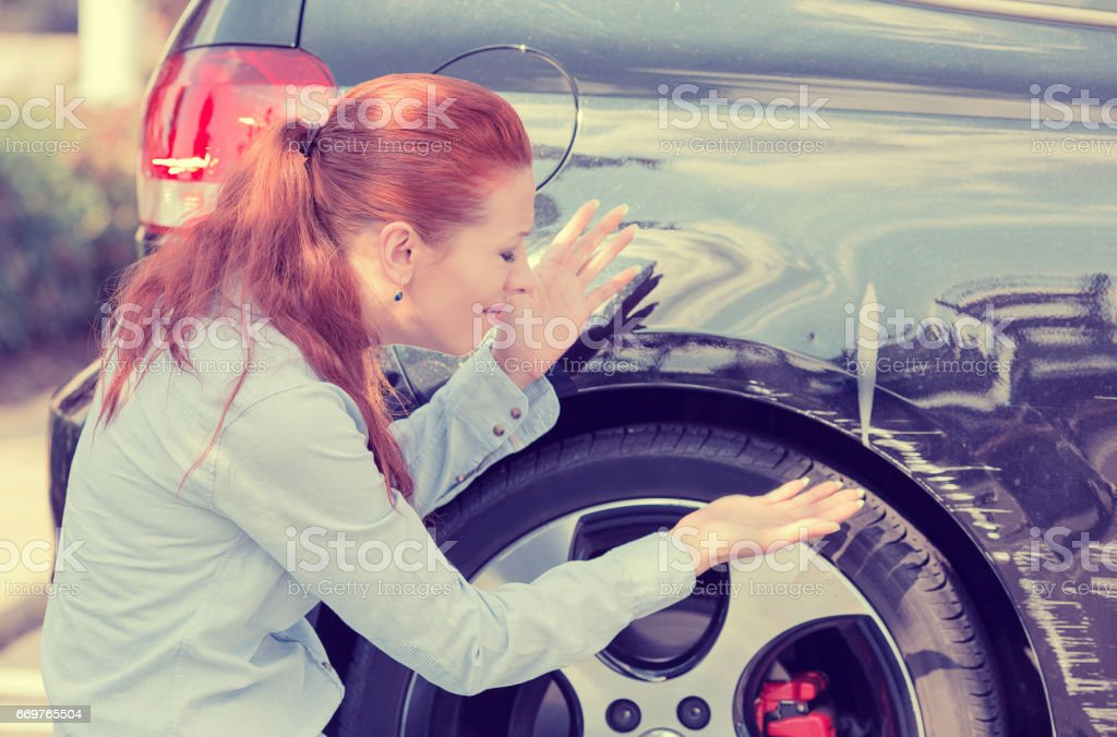 Frustrated young woman checking pointing at car scratches and dents outdoors outside stock photo