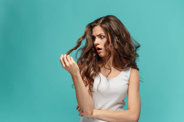 frustrated young woman having a bad hair on blue - messy hair stock photos and pictures