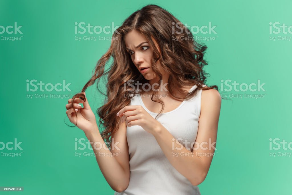 Frustrated young woman having a bad hair on blue stock photo