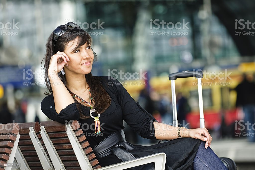 Frustrated Young Woman Sitting on Train Station Bench royalty-free stock photo