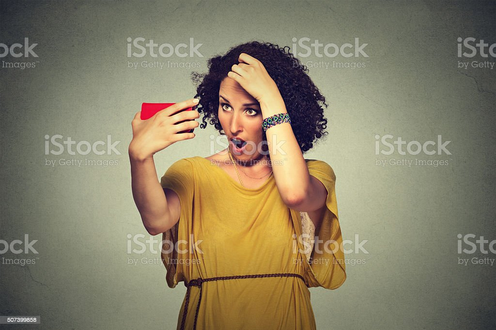 frustrated young woman surprised she is losing hair stock photo